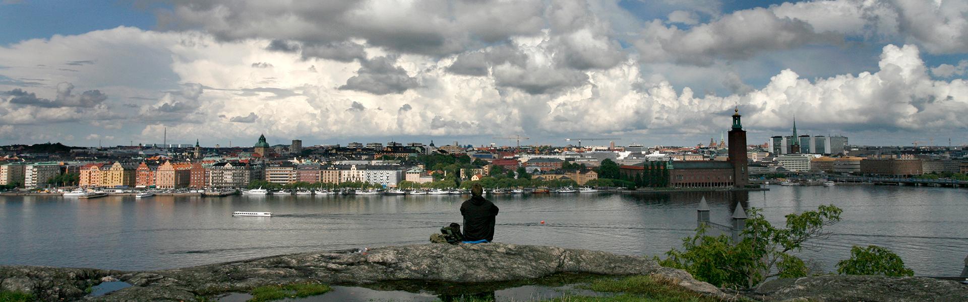 Person sitter på en stenhäll och ser ut över Stockholm. Foto: Yanan Li.