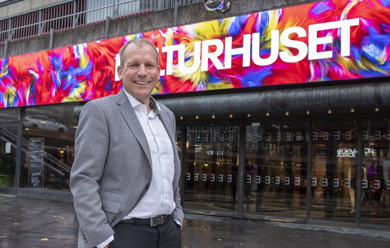 Kulturhuset Stadsteaterns vd Jesper Larsson framför den enorma digitalskylten som med specialgjorda konstverk visar glimtar av vad huset har att bjuda på.